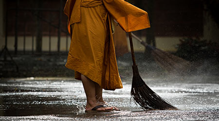 thai monk daily cleaning in buddhist temple