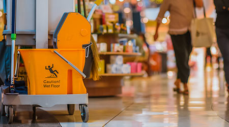 Yellow mop bucket floor cleaning equipment and mops in shopping mall and department store