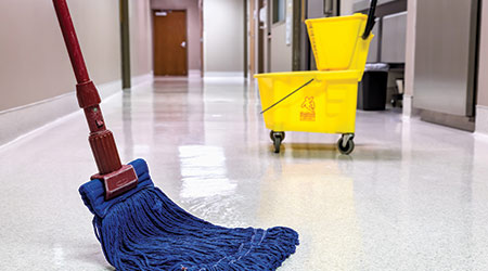 Mopping wet floor in hospital with bucket