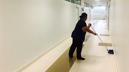 Women janitor mopping floor interior of new building