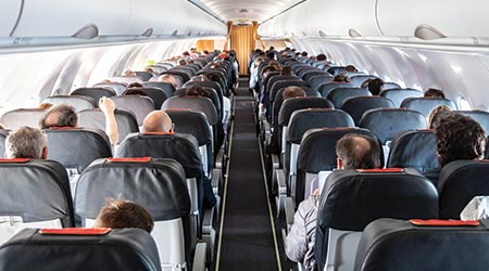 Interior of commercial airplane with unrecognizable passengers on their seats during flight shot from the rear of airplane