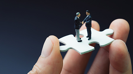 miniature people businessmen handshaking on white jigsaw puzzle piece in real human hand, dark black background