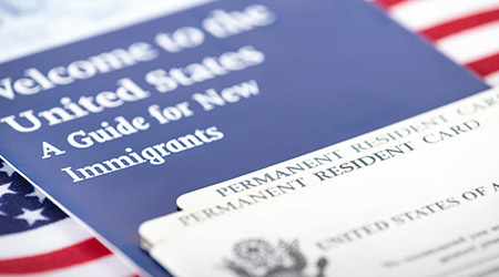 United States of America permanent resident cards, green card, with US flag on the background. Immigration concept.