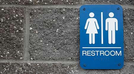 Unisex Bathroom sign on brick wall