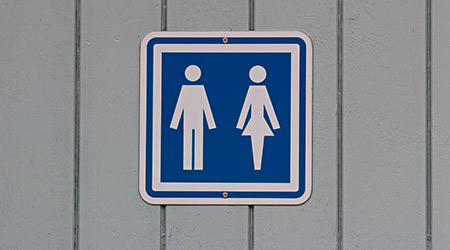 A blue male and female restroom sign