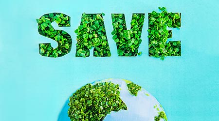 Creative concept with outline lettering Save in green fresh grass sprouts and part of planet model on blue turquoise background