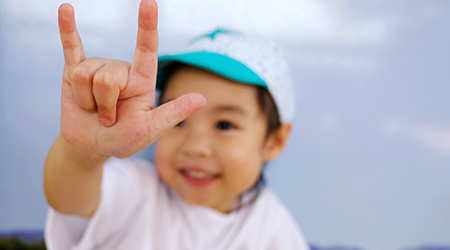 An adorable little asian girl show her hand, the sign hand language