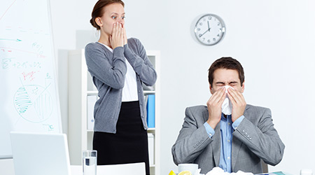 businessman sneezing while his partner looking at him with fright in office