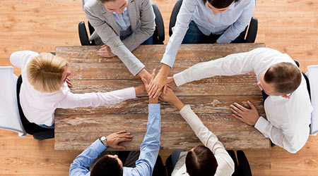 close up of creative team sitting at table and holding hands on top of each other in office