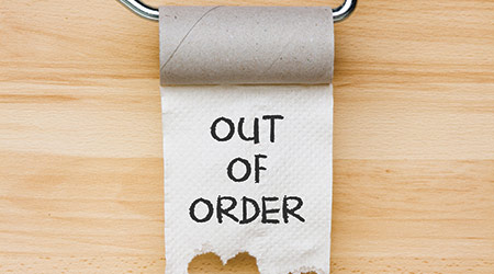 Toilet paper on wooden background saying restroom out of order