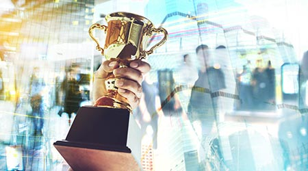 Man holding up a gold trophy cup is winner in a competition with cityscape background