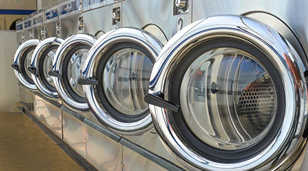 Row of industrial laundry machines in laundromat