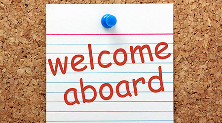 The phrase Welcome Aboard printed on a lined index card and pinned to a cork notice board