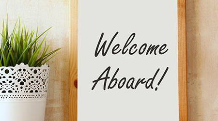 drawing board with the phrase welcome aboard handwritten over wooden table