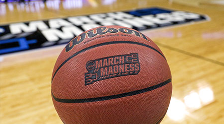 A game ball with the NCAA tournament logo in the background