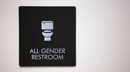 All Gender Restroom logo adorns the side of a restroom