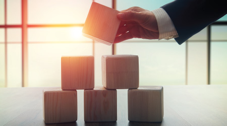 The concept of planning in business. Wooden cubes on a desk in the office. The concept of leadership. Hand men in business suit holding the cubes.