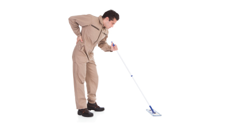 Janitor mopping and holding his back in pain