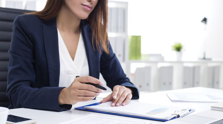Woman prepares to write something on a piece of paper