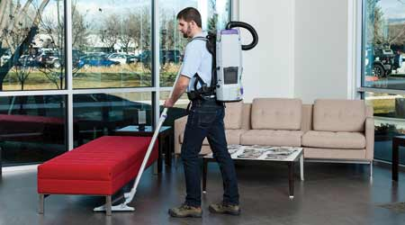 Janitor cleans office with backpack vacuum