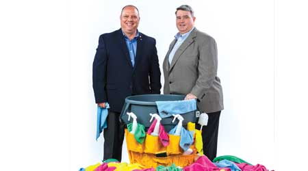 Two men in suits pose near a pile of rags