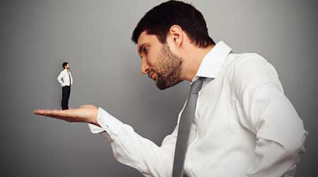 Shrunken business man stands on the hand of a normal size man