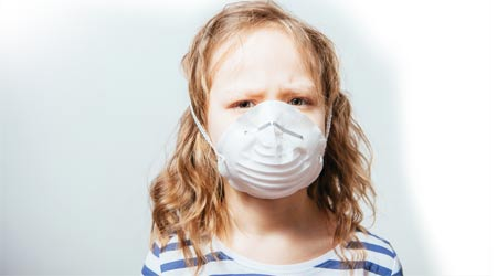 young girl with medical mask over her face protecting her from poor indoor air