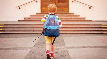 small child walking into a k12 school on first day