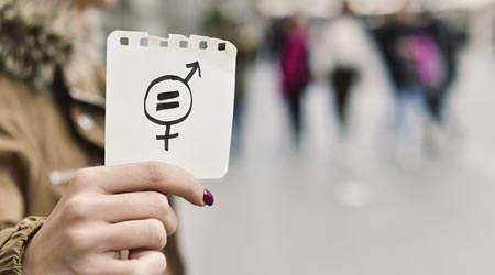 Person holds paper showing gender equality symbol