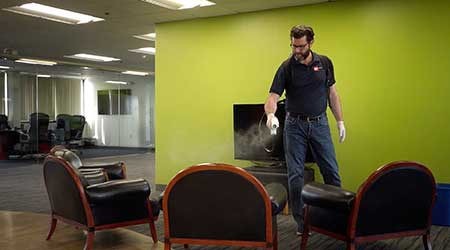 man sprays disinfectant on office chairs