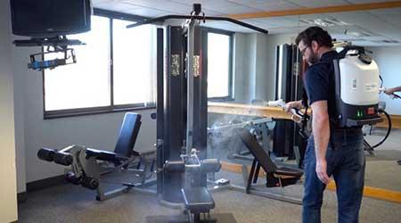Man cleans gym equipment