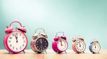 Five retro alarm clocks with last minutes to twelve o'clock on wooden table front gradient mint green wall background