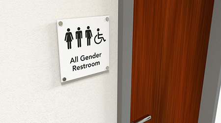 All-gender restroom signage next to a wooden restroom door showing icons of man, woman, transgender and wheelchair user