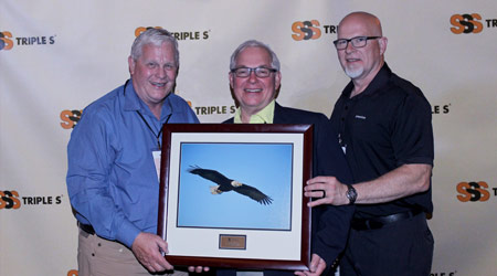Three old men hold photo of an eagle