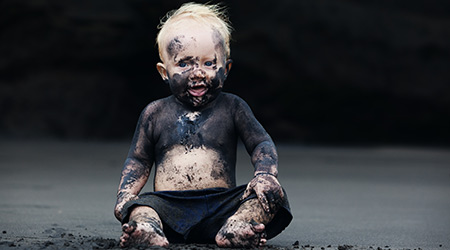 smiling child with dirty face sitting and playing with fun on black sand sea beach