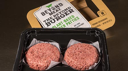 Packagingand contents of Beyond Meat Beyond Burgers on steel background