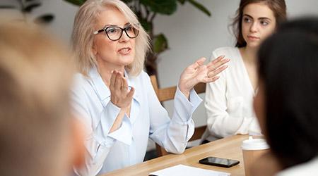 senior woman in glasses teaching audience at training seminar