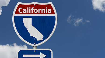 Red, white and blue interstate highway road sign with word California
