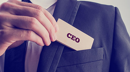 Retro style image of a businessman showing a wooden card reading - CEO - as he withdraws it from the pocket of his suit jacket