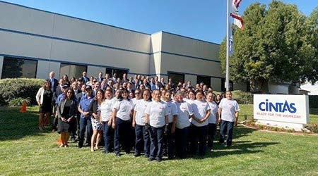 A large group of Cintas employees in white shirts in front of a Cintas office in California