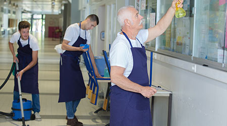 janitorial services cleaning the windows, vacuuming the foor and disinfecting the surface