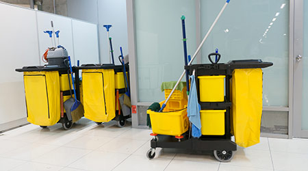 Cleaning Cart in the station. Cleaning tools cart and Yellow mop bucket wait for cleaning. Bucket and set of cleaning equipment in the airport office