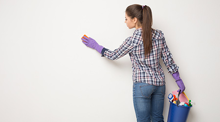 Woman wiping white wall from dust with dry rag