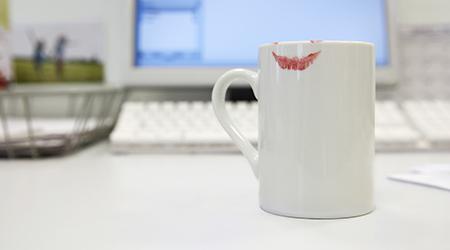 Lipstick print on coffee mug on computer desk