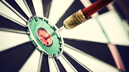 Dart arrow hitting in the target center of dartboard
