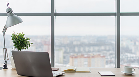 Comfortable work table in office windows and city view