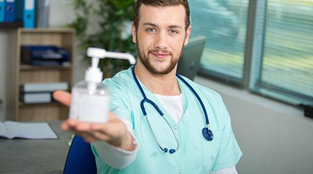 doctor holding pump dispenser of antibacterial handwash