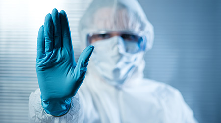 Scientist with hand raised in hazmat protective suit, stop concept