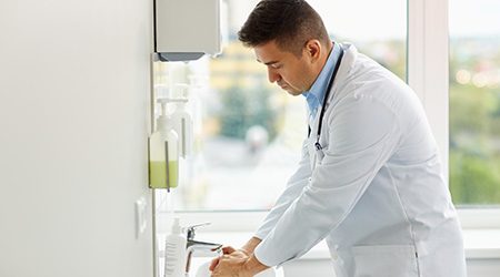 doctor washing hands at medical clinic sink