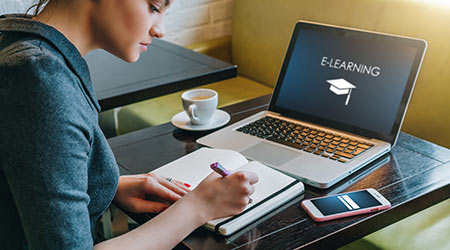 Young businesswoman sitting at table in cafe in front of laptop with inscription on screen e-learning